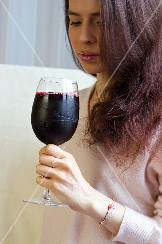 A woman drinking vitamin juice made with beetroot, pear, red cabbage and rose petals