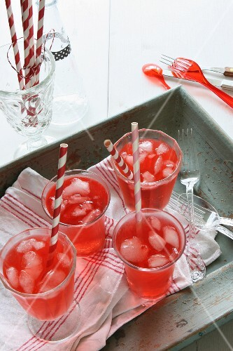 Red lemonade with ice cubes and straws on a wooden tray