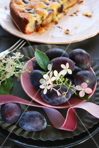 A bowl of plums in front of a sliced plum cakes