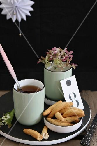 Savoury snacks, mug of tea and stem of flowers on black wooden board against dark background