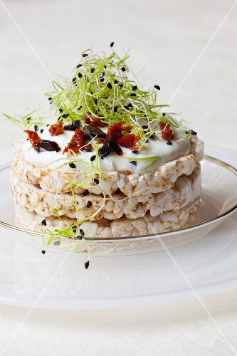 Rice waffles topped with quark, olives, dried tomatoes and bean sprouts