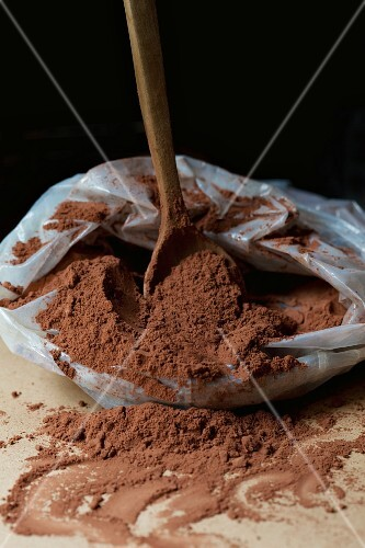 A wooden spoon in a plastic bag of cocoa powder