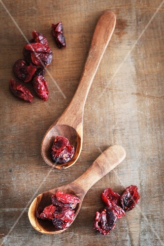 Dried cranberries and two wooden spoons
