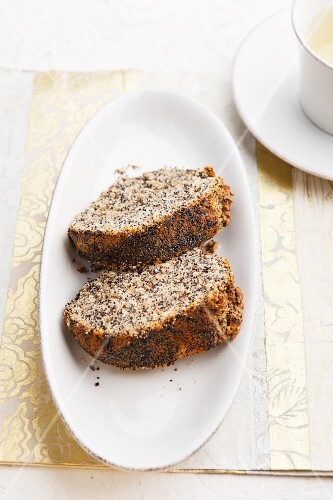 Two slices of poppy seed Bundt cake with a cup of tea