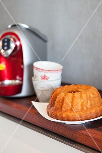 A Bundt cake next to a coffee machine