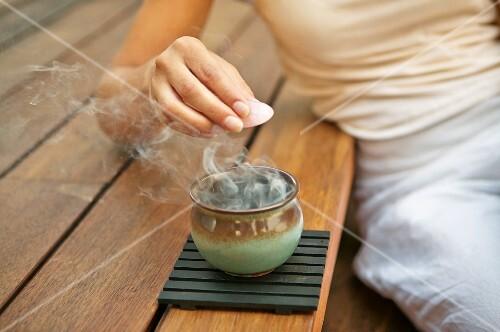 Woman holding healing stone above smoking incense bowl