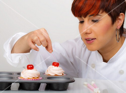 A woman decorating cupcakes