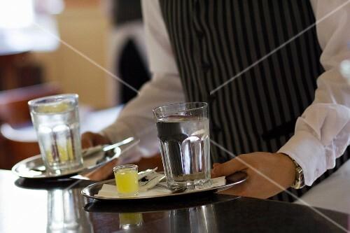 Kellner serviert Tabletts mit Wasser und Zitronensaft im Cafe