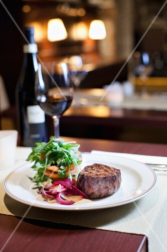 a view on the interior of the restaurant, a table with wine, a dish of sirloin steak with red onions, tomatoes and rocket leaves