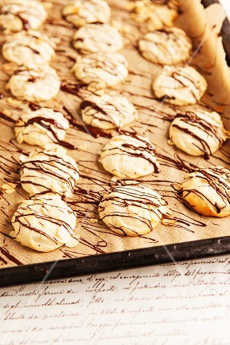 Macaroons drizzled with chocolate on a baking tray