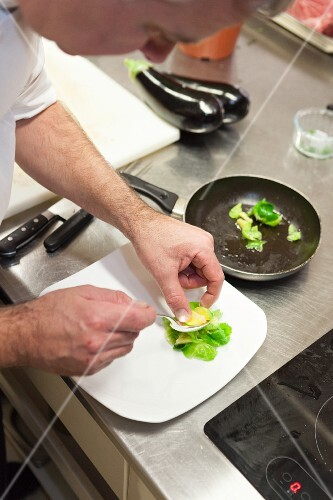 Brussels sprouts being arranged on a plate