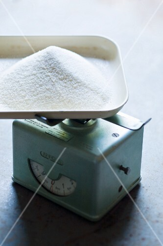 A pile of sugar on a old kitchen scale