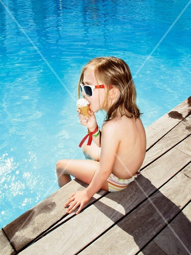 Girl Eating Ice Cream Cone at Edge of Swimming Pool
