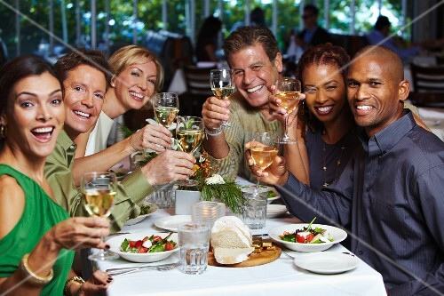 Friends raising wine glasses whilst eating together in a restaurant