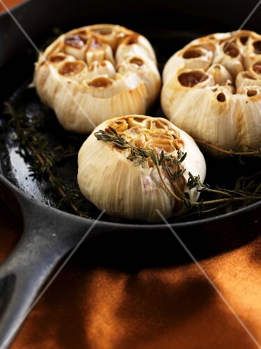 Roasted garlic bulbs with thyme in a pan