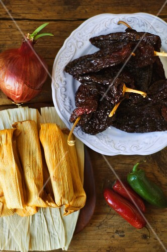 An arrangement featuring tamales, an onion and fresh and preserved chillis