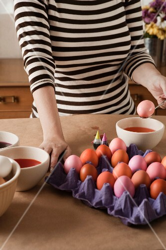A woman colouring Easter eggs
