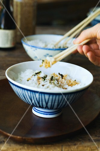 A person eating rice with chopsticks
