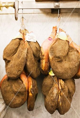 Whole Parma hams hanging on hooks to be sold
