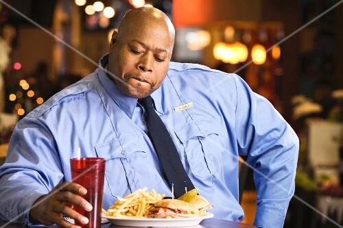 A dark-skinned, overweight policeman eating fast food