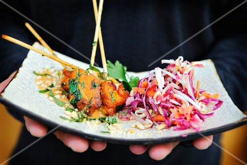 A person holding a serving platter with kebabs and salad (Thailand)