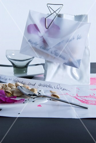 Translucent envelope filled with sesame seeds and petals clipped to vase shaped like paper bag with paper clip