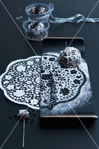A print of a doily in icing sugar with a chocolate cake on an elegant plate