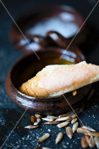 A piece of bread dipped in olive oil with sunflower seeds