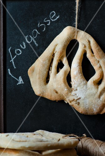 A single Fougasse bread hanging with a sign written in chalk behind.