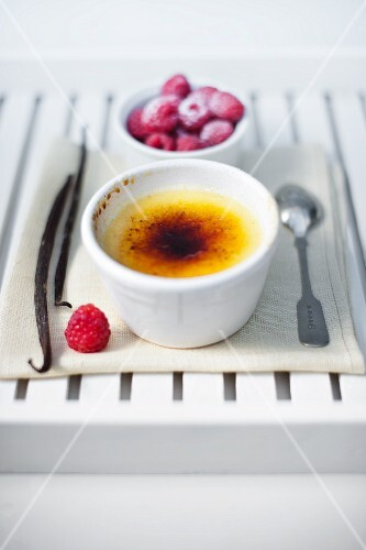 A single pot of vanilla creme brulee with fresh raspberries and vanilla pods.
