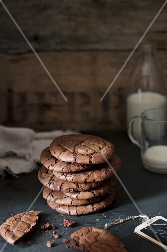 a stack of dark chocolate cookies one crumbled and a bottle of milk and a cup in a background.