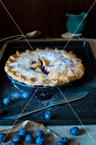 Blueberry Pie on a metal tray with jug of cream and fresh blueberries