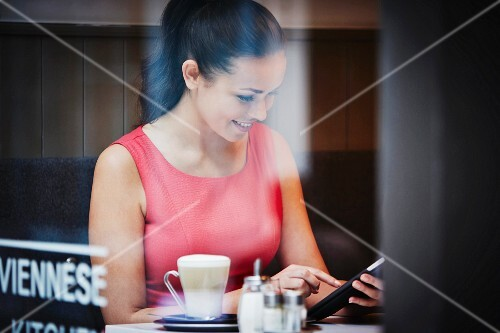 A young woman with a tablet computer and a hot drink in a cafe