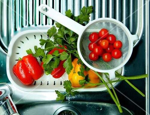 Fresh cherry tomatoes, peppers and parsley on a drainer
