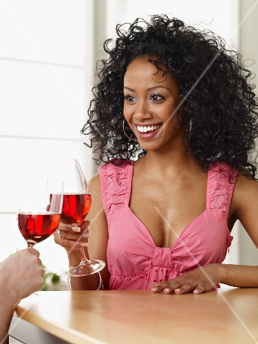 Young woman drinking glass of rosé wine.
