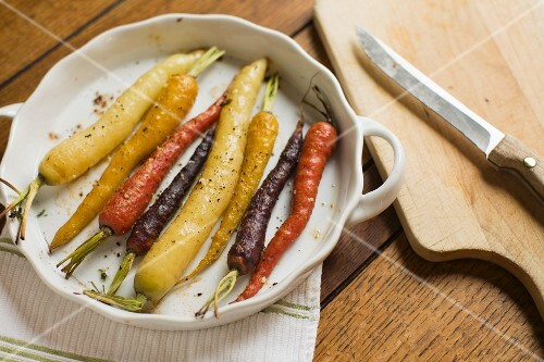 Roasted multi-color carrots in a white scalloped dish with knife and cuting board
