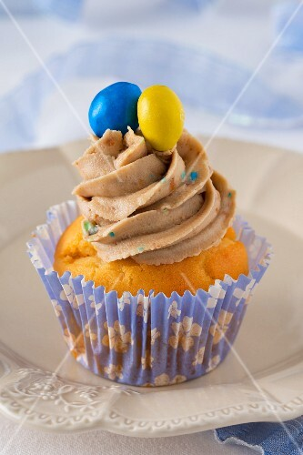 A cupcake decorated with buttercream and coloured chocolate beans