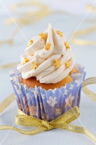A cupcake decorated with a gold bow and stars for Christmas