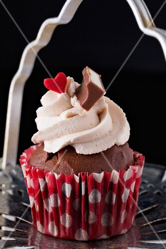 Chocolate cupcake decorated with strawberry cream and a red heart