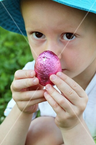 A little boy holding a chocolate Easter egg