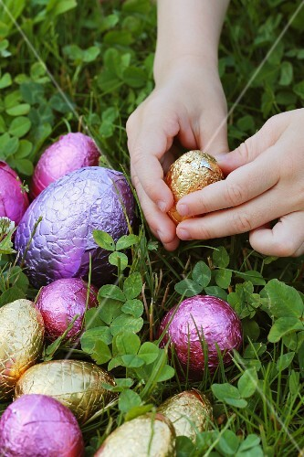 Child's hand reaching for a chocolate egg in a field