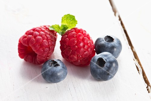 Raspberries and blueberries on a white wooden table
