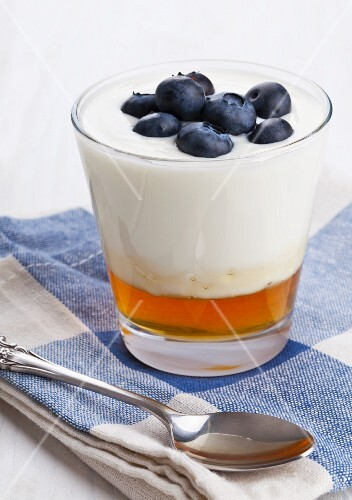 Natural yogurt on honey topped with blueberries in a glass