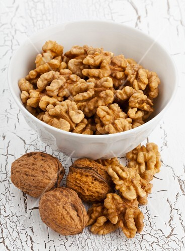 A bowl of walnuts with a whole nuts and shelled nuts in front of it