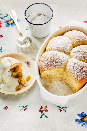 Apple filled Buchteln (baked, sweet yeast dumpling) with icing sugar and vanilla sauce