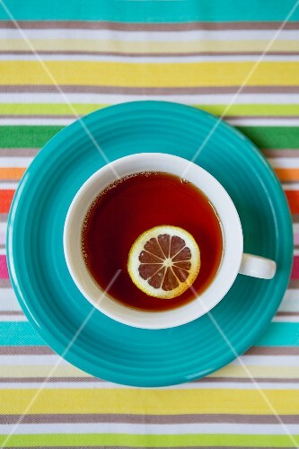 Cup of Tea With Slice of Lemon on Blue Plate and Striped Tablecloth, High Angle View