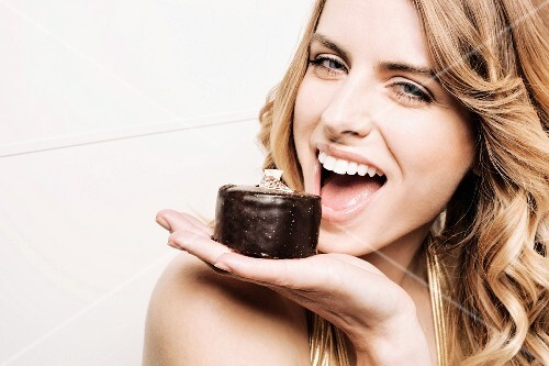 Model holding cake to mouth