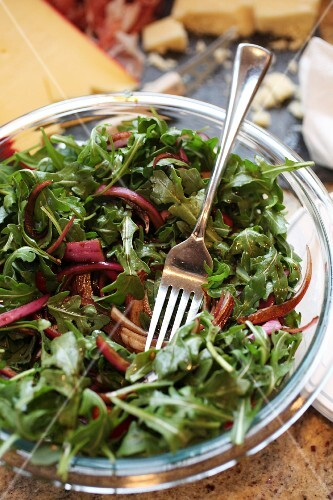 Bowl of arugula salad with balsamic marinated red onions