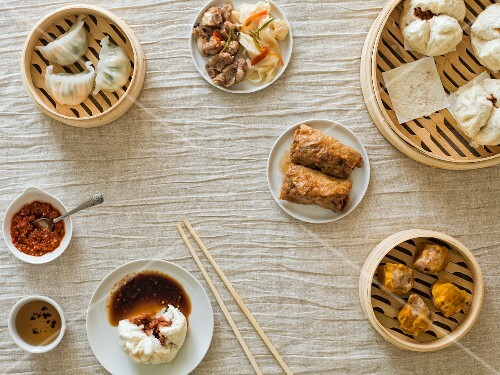 Overhead of bamboo steamers with various dim sum dumplings and sauces on a light material with chopsticks