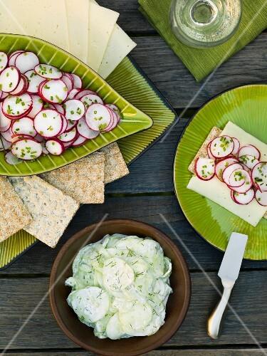 Cucumber salad, radish salad, crisp bread and slices of cheese